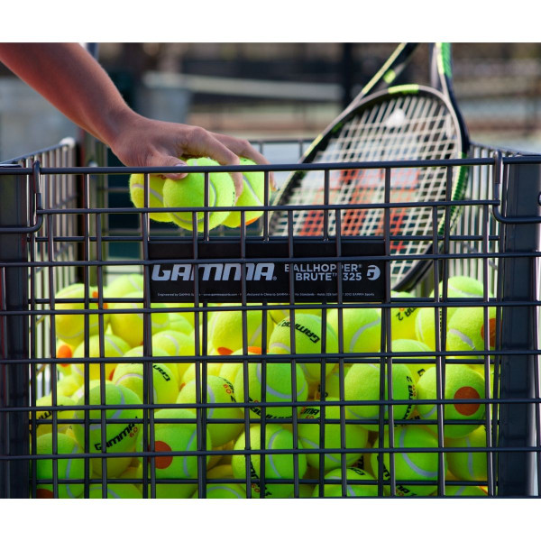 Person dropping 3 tennis balls into the GAMMA Brute 325 Teaching Cart.