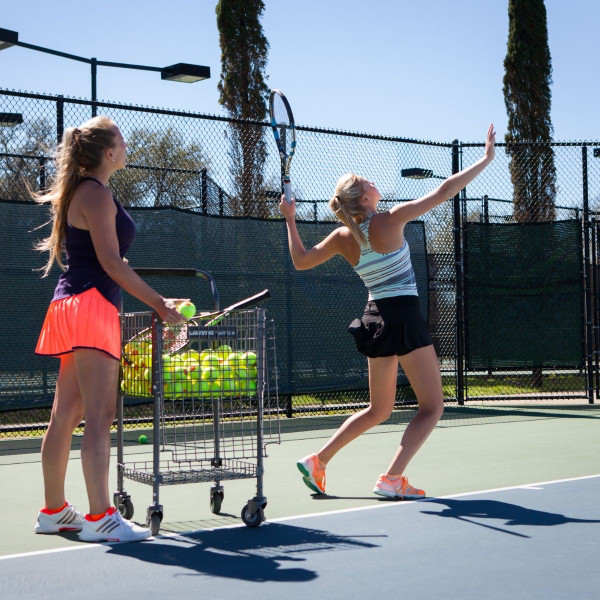 Girl swinging at a tennis balls and her instructor is standing by the GAMMA Brute 325 Teaching Cart.