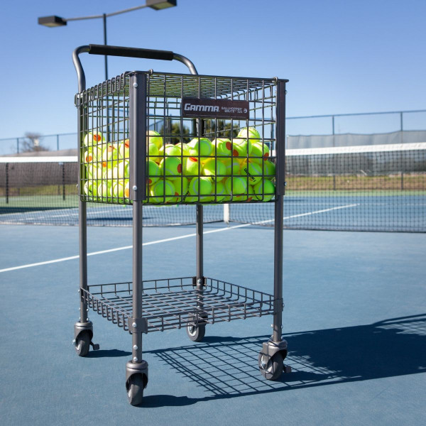 The GAMMA Brute 325 Teaching Cart featured on a tennis court filled with GAMMA Orange Dot Tennis Balls.