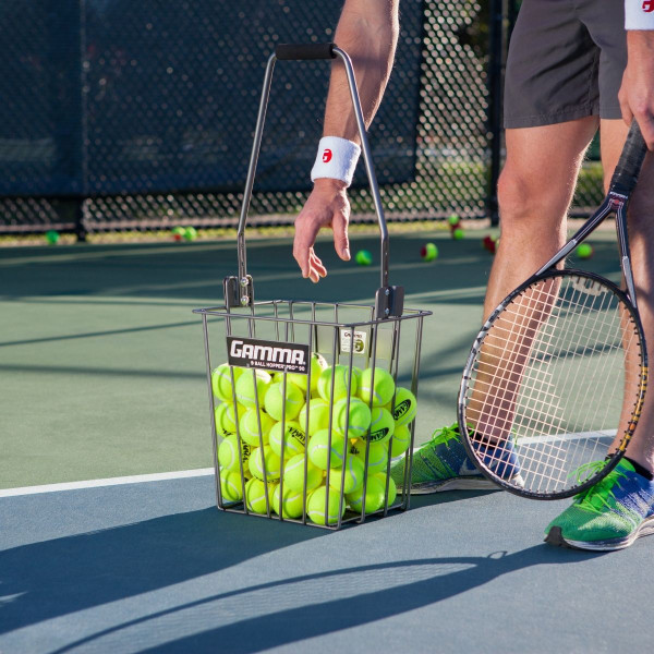 Tennis player bending over to pick up a tennis ball out of a Ball Hopper Pro 90.