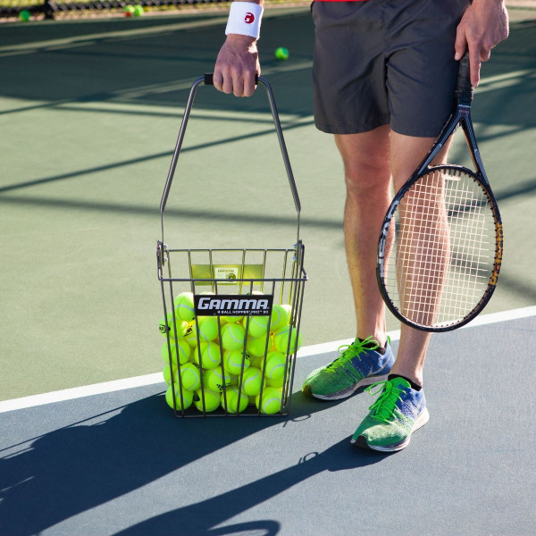 Tennis player picking up a Ball Hopper Pro 90 by its carrying handle.