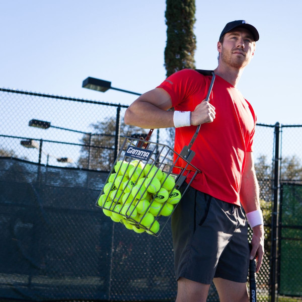 Tennis player using the handle of the Ball Hopper Pro 90 to carry it on his shoulder.