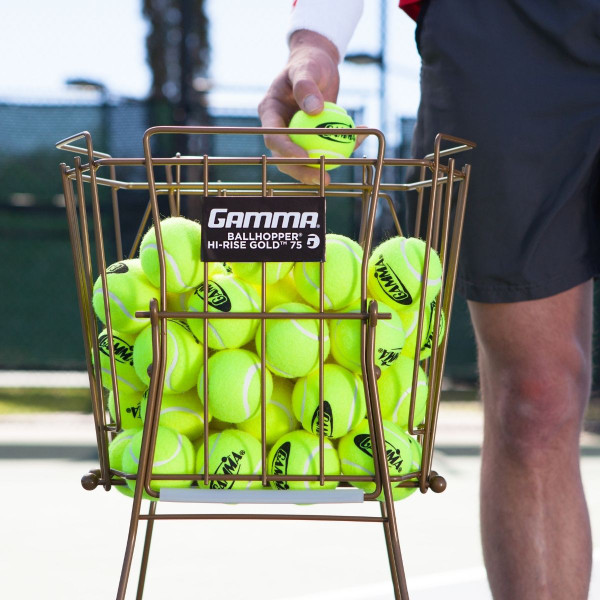 Player picking up a tennis ball out of the Ballhopper Hi-Rise Gold 75.