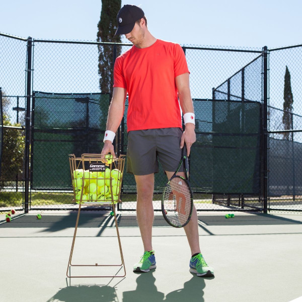 Player picking up a tennis ball out of a Ballhopper Hi-Rise Gold 75 that is filled with tennis balls.