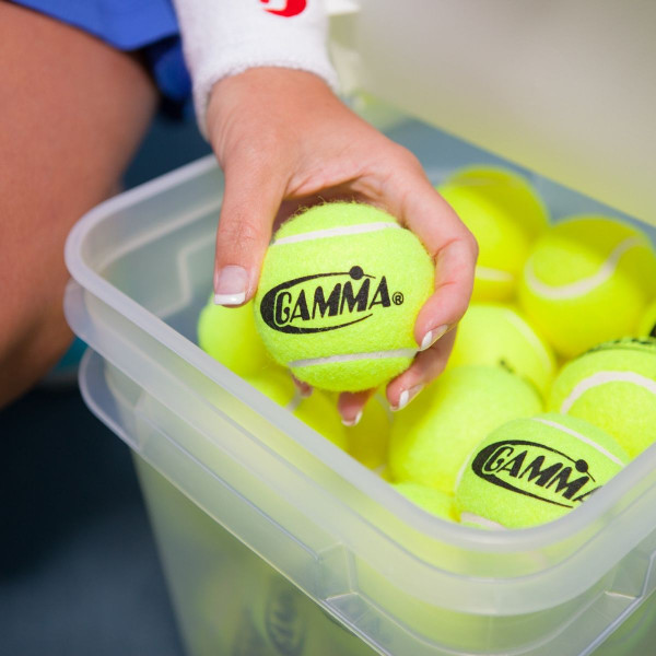 A person's hand picking up a Yellow Pressureless Tennis Ball out of a GAMMA Bucket-O-Balls.