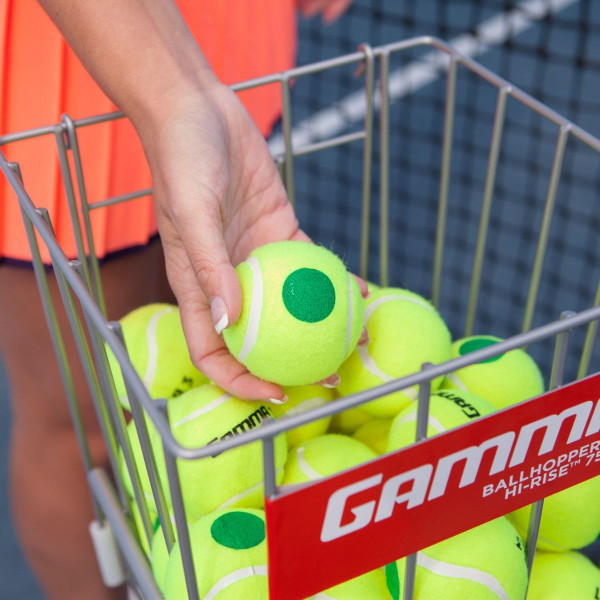 A girl grabbing a GAMMA 78 Green Dot Tennis Ball out of a ball hopper basket filled with GAMMA 78 Green Dot Tennis Balls.
