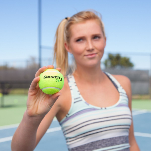A young girl holding a GAMMA 78 Green Dot Tennis Ball in her hand.