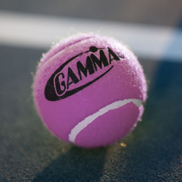A Pink GAMMA Pressureless Practice Ball for Tennis Placed On A Tennis Court.