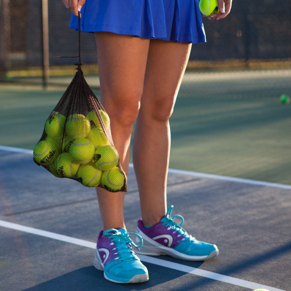 Girl holding a mesh bag by its draw string. The bag is filled with 12 Yellow Pressureless Tennis Practice Balls.