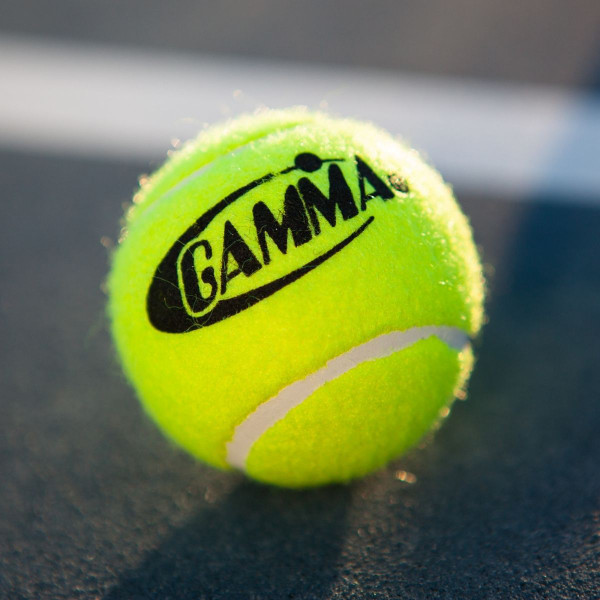 A Yellow GAMMA Pressureless Practice Ball for Tennis Placed On A Tennis Court.