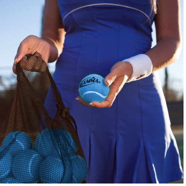 Girl holding a mesh bag filled with 18 Blue Pressureless Tennis Balls in one hand and a single Blue Pressureless Ball in the other.