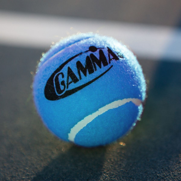 A 18 Blue GAMMA Pressureless Tennis Ball Positioned On A Tennis Court