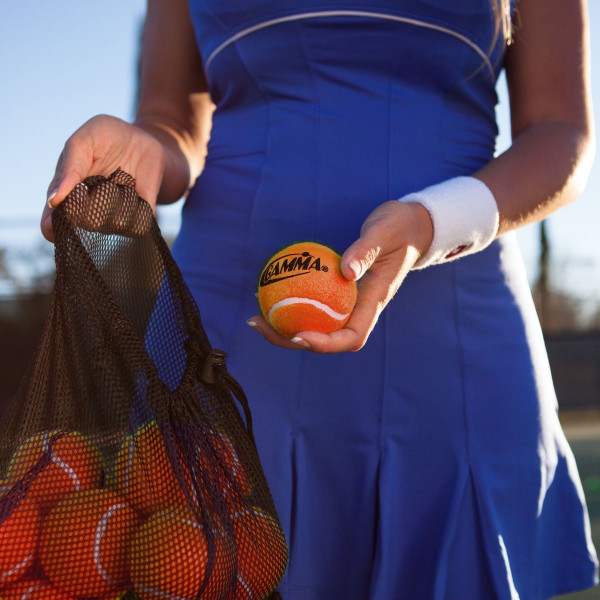 Girl holding a mesh bag filled with 18 Orange Pressureless Tennis Balls in one hand and a single Orange Pressureless Ball in the other.