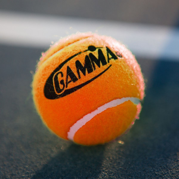 An Orange GAMMA Pressureless Practice Ball for Tennis Placed On A Tennis Court.