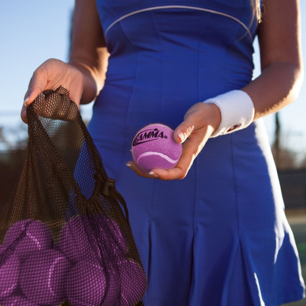 Girl holding a mesh bag filled with 18 Pink Pressureless Tennis Balls in one hand and a single Pink Pressureless Ball in the other.