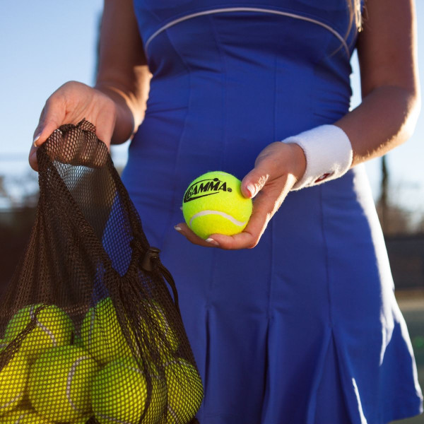 Girl holding a mesh bag filled with 18 Yellow Pressureless Tennis Balls in one hand and a single Yellow Pressureless Ball in the other.
