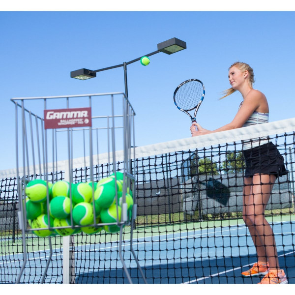 A Ball Hopper Full of GAMMA Quick Kids 78 Tennis Balls and a Girl Hitting a GAMMA Quick Kids 78 Tennis Ball Over A Tennis Net In The Background