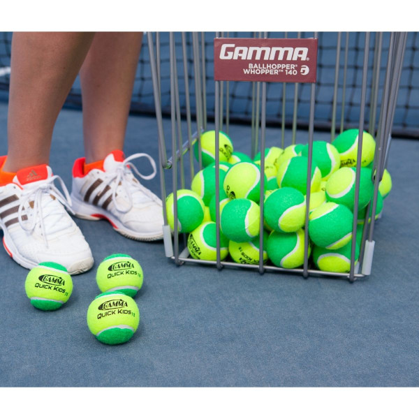 Ball Hopper Full of GAMMA Quick Kids 78 Tennis Balls And 3 Lying On Court In Front of Player's Feet