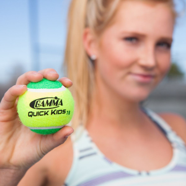 Girl Holding Out Her Hand Towards Camera Showing Off the GAMMA Quick Kids 78 Tennis Ball