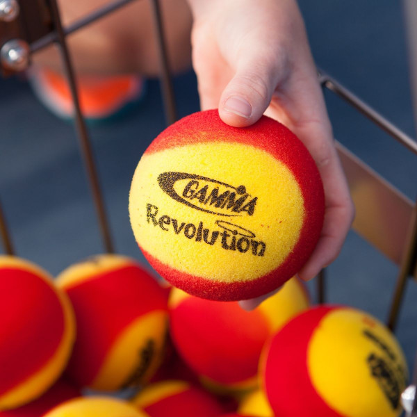 Person's Hand Holding A GAMMA Revolution Foam Ball Over A Basket Full of GAMMA Revolution Foam Balls.