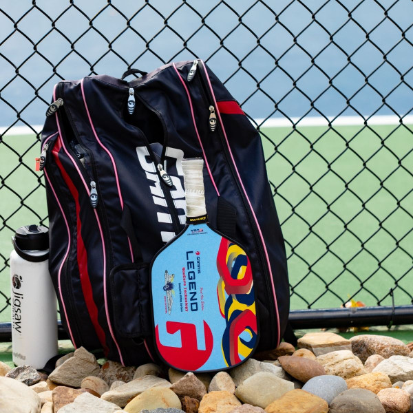 Paul Olin Edition GAMMA Legend NeuCore Pickleball Paddle laid up against a GAMMA Pickleball Paddle Bag