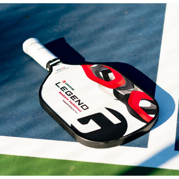 White GAMMA Legend NeuCore Pickleball Paddle lying on a pickleball court